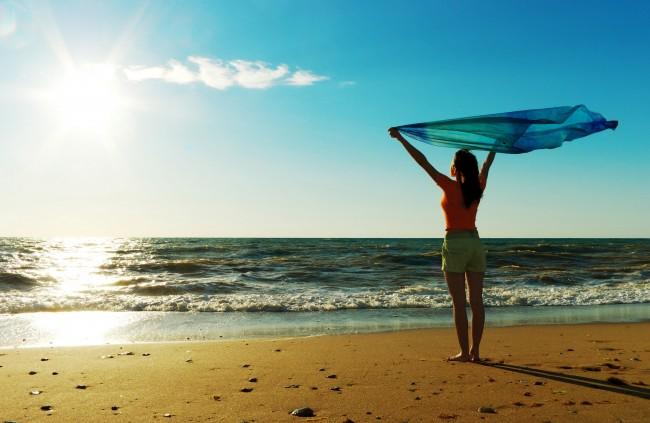 Девушка с развивающимся платком в руках на берегу моря
