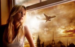 Девушка смотрит в окно на улетающий самолёт