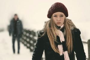 Девушка зимой и силуэт парня за её спиной