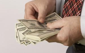 Мужчина держит пачку денег