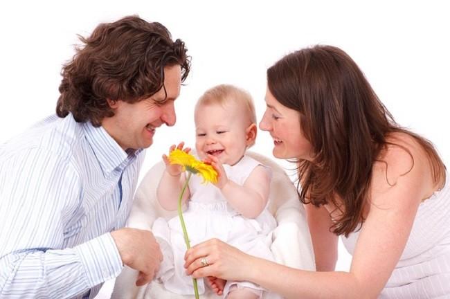 Родители с маленьким ребёнком и цветком