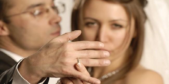 Женщина смотрит на обручальное кольцо мужчины