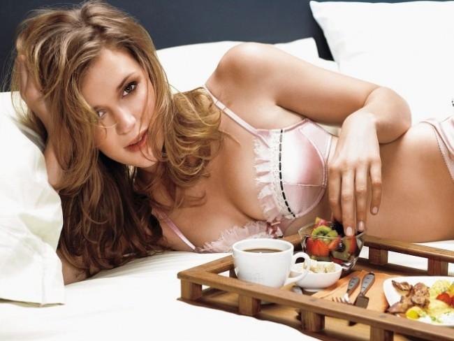 Девушка в красивом белье рядом с подносом с десертом