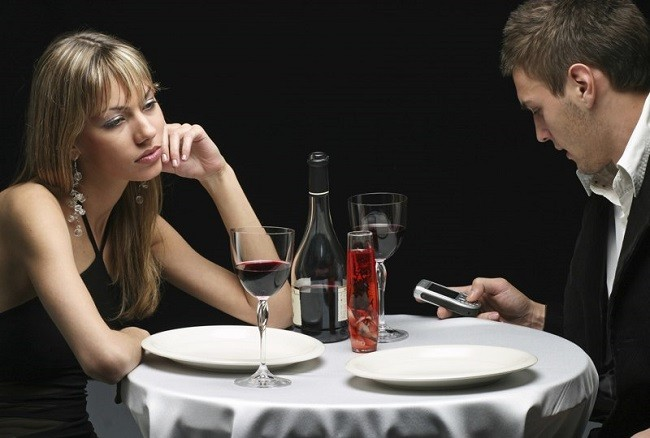 Мужчина смотрит в телефон, а не на свою спутницу
