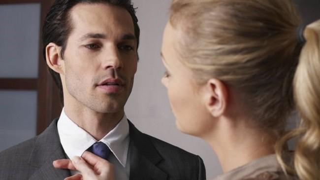Женщина поправляет мужчине рубашку