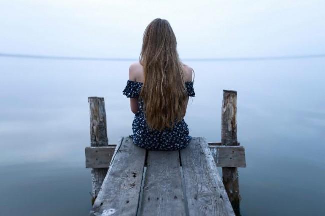 Девушка сидит на мостках и смотрит на море