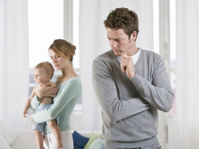 Мужчина сердится, повернувшись спиной к женщине с ребёнком