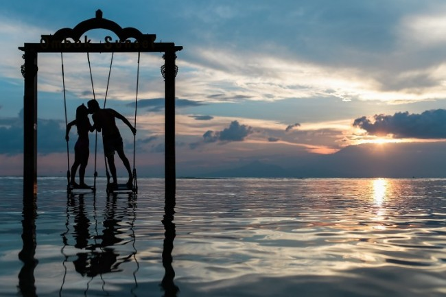 Пара на качелях над водой