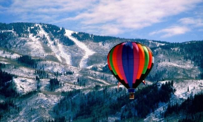 Полёт на воздушном шаренад заснеженным лесом