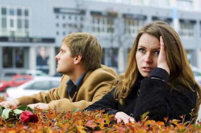 Рассерженная девушка сидит спиной к мужчине