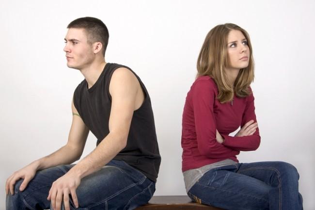 Сердитые парень и девушка сидят спиной друг к другу