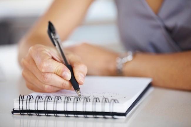 Женская рука пишет что-то в блокноте