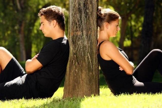 Мужчину и женщину, сидящих спиной к друг другу, разделяет дерево