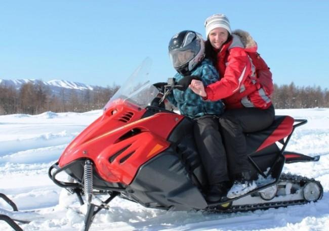 Молодая пара на снегоходе