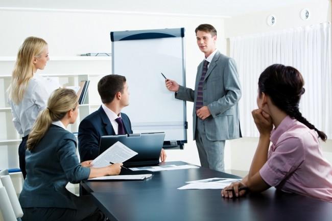Молодой человек объясняет что-то коллегам