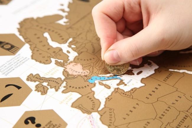 Рука стирает со скетч-карты цветной слой