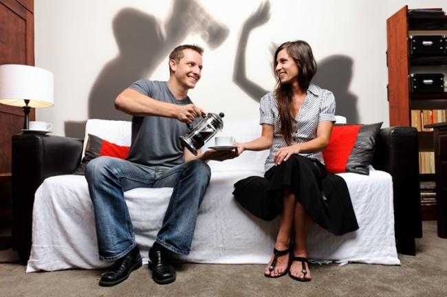 Мужчина и женщина пьют чай, а их тени на стене дерутся